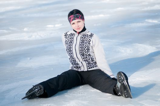 Ice skating woman sitting on ice
