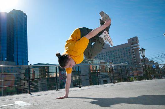 Teenage hip-hop girl dancing over city landscape