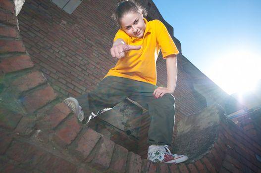 Teenage hip-hop girl on red brick wall