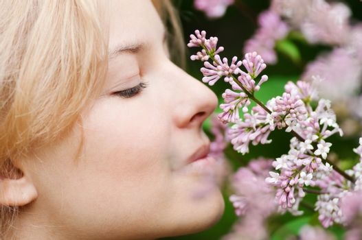 Woman with lilac flower on face