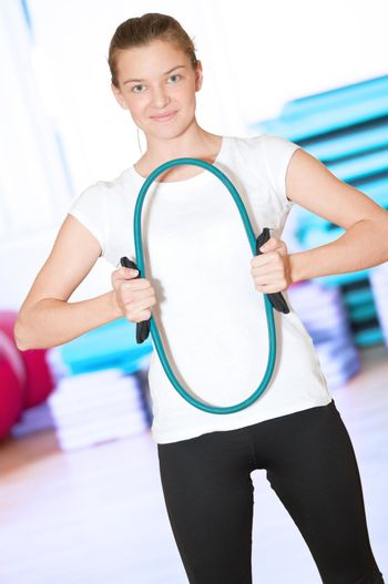 Beautiful sport woman doing power fitness exercise at sport gym. Expander