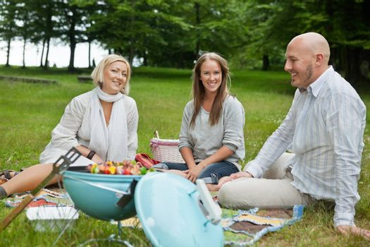 Happy Caucasian friends on picnic with portable barbeque in forest park