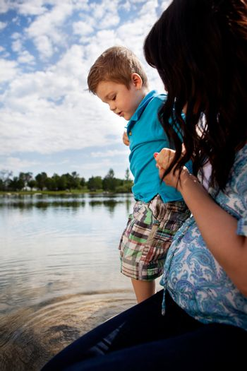 Pregnant mother with young son playing in small pond in park