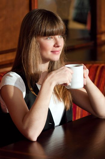 A woman sitting in a cafe with a coffe
