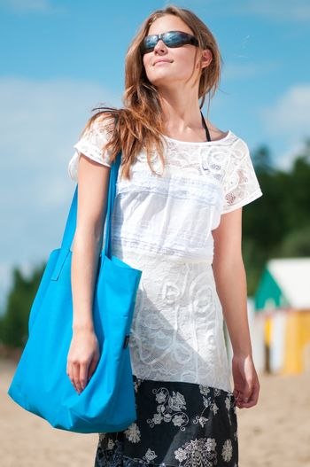 woman walking on sand beach with bag