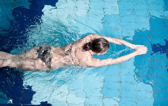 Athletic swimmer is diving in a swimming pool