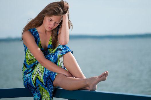 sad woman sitting over sea at summer day