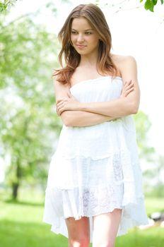 Beautiful young woman relaxing in apple tree garden