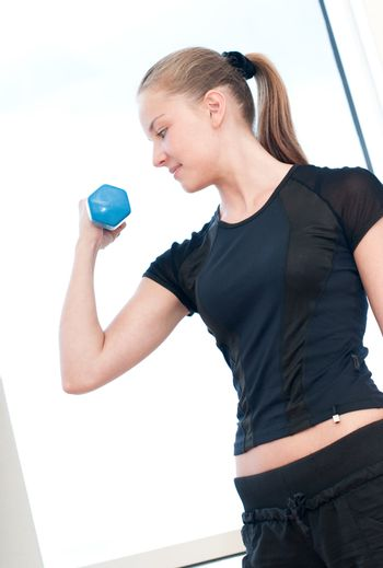 Young woman doing dumbbell exercises