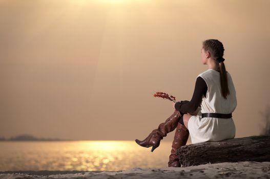 Lonely woman sitting on lake coast