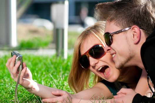 Emotional teenage couple photographing outdoor