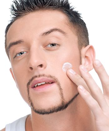 Handsome man applying male creme on face