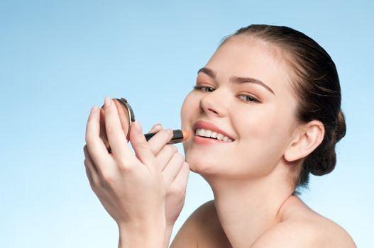Beautiful young adult woman applying cosmetic lipstick