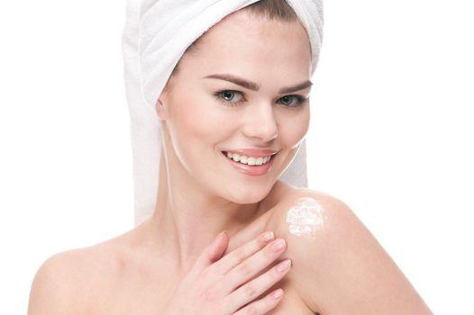 Woman applying moisturizer cream on shoulders