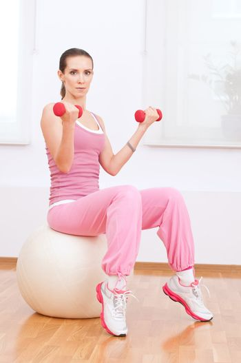 Beautiful sport woman doing dumbbell fitness exercise at sport gym