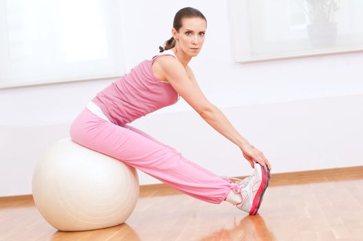 Woman doing stretching exercise on ball