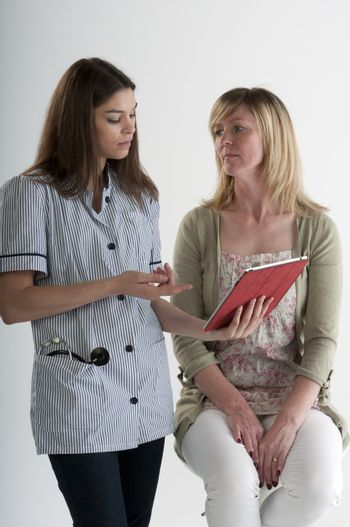 Nurse using an iPad talking to a female patient