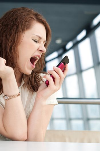Emotional Business woman with phone at cafe