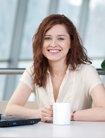 Business woman with a laptop and mug