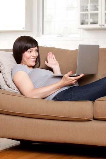 Happy pregnant woman talking on internet video chat