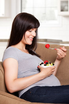 Happy smiling pregnant woman sitting on sofa eating fresh fruit