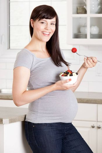Happy pregnant woman eating a healthy snack of granola and fruit