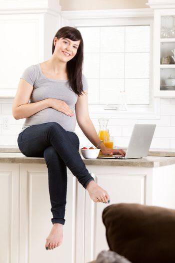 Healthy pregnant woman sitting on kitchen counter eating snack
