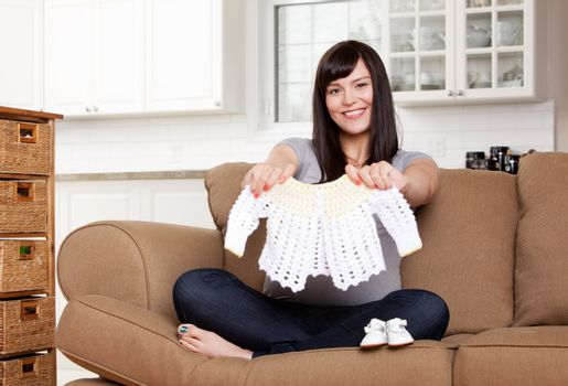Portrait of expecting mother holding up knitted sweater