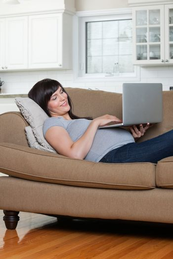 Happy pregnant woman using laptop while lying on sofa