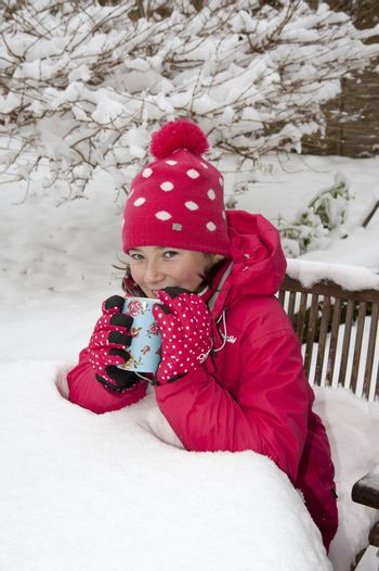 Young girl enjoying a warm drink sitting on snow covered garden furniture
