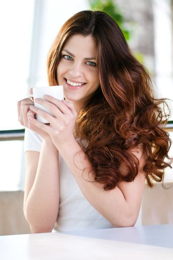 Woman sitting in a cafe with a coffe