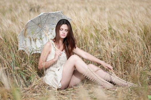lonely woman sitting in wheat field