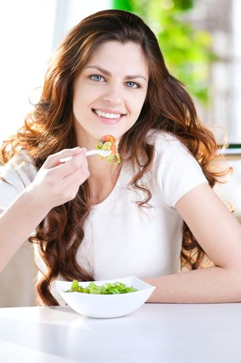 A young woman in a cafe with a coffe with salad