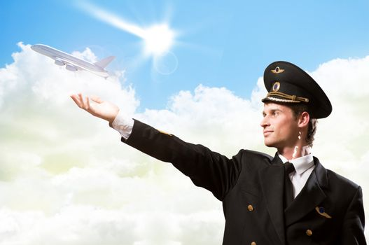 pilot in the form of extending a hand to a flying airplane on the background of clouds and sun