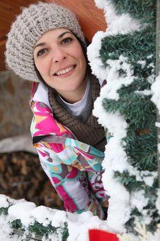 Woman behind snowy tree