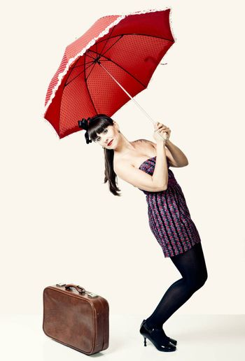 Beautiful woman with a vintage look posing with a red umbrella