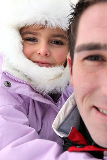 Portrait of a man with little girl by wintertime