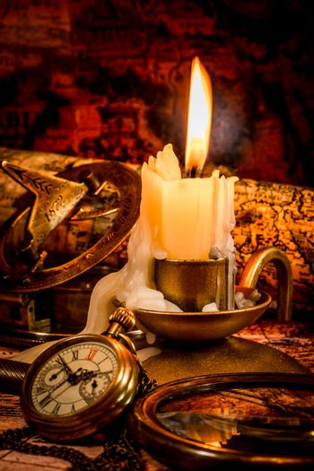 Vintage compass, pocket watch lie on an old ancient map with a lit candle