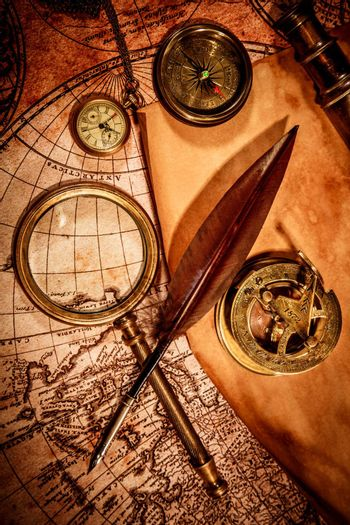 Vintage magnifying glass, compass, goose quill pen, spyglass and a pocket watch lying on an old map.