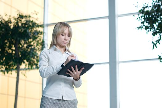 Young businesswoman with day planner in lobby