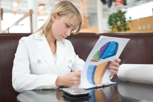 Young businesswoman with charts in cafe