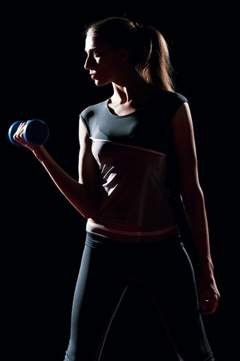 Beautiful sport woman doing power fitness exercise at sport gym. Dumbbell on black