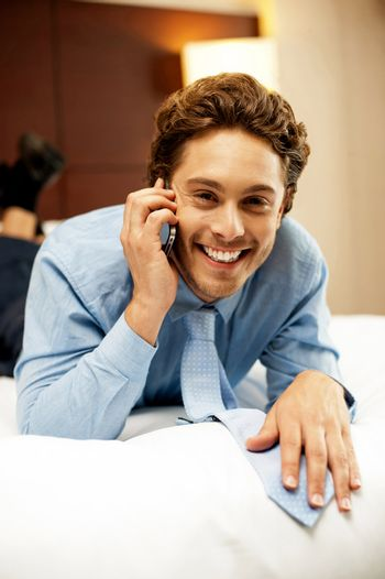 Relaxed young businessman communicating with his partner