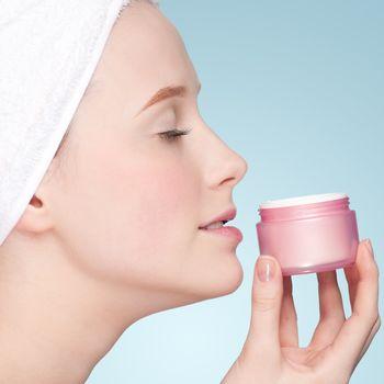 Beautiful woman smell jar of moisturizer cream