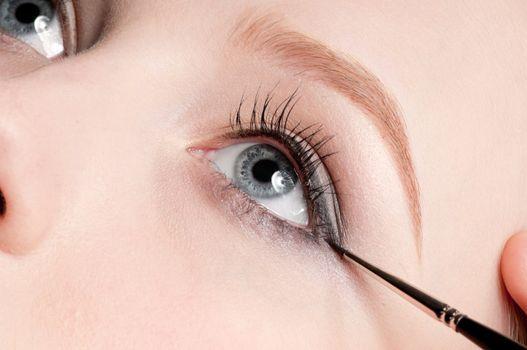 Beautiful young adult woman applying cosmetic brush