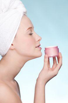 Beautiful woman tender jar of moisturizer cream. Close-up fresh young woman face