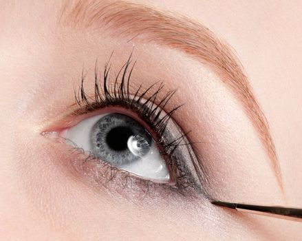Beautiful young adult woman applying cosmetic paint brush - close-up portrait of eye shadow zone