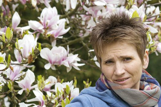 portrait of woman with blooming magnolia on background
