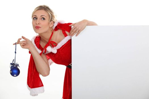 Woman dressed as Mrs. Claus and holding a blank board