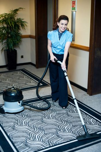 Staff cleaning carpet with a vacuum cleaner
